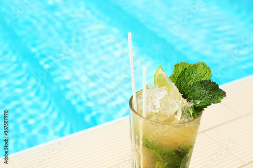 Obraz Glass of delicious mojito near swimming pool, space for text. Refreshing drink - fototapety do salonu