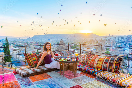 Photo A woman have breakfast on one of the Cappadocia roof in early morning sunrise, when balloons fly