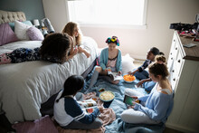 Teenage Girls Enjoying Sleepover, Reading Magazines And Snacking In Be