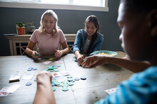 Teen Friends Playing Cards At Dining Table