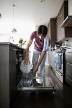 Teenage Boy Doing Dishes In Ki...