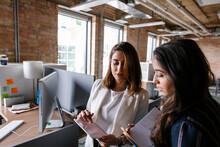Businesswomen With Digital Tablet Talking In Office