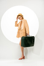 Trendy Positive Woman Holding Green Travel Bag Near Circle On White Background