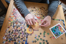 Man Assembling Jigsaw Puzzle On Table