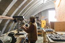 Male Carpenter Using Drill Pre...
