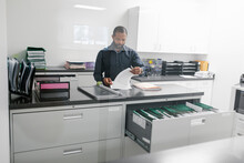 Mature Man Looking At Files In Office