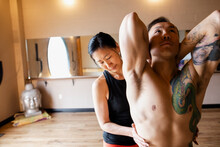 Yoga Instructor Helping Studen...