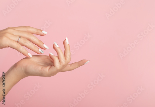 Fotografía Hands of a beautiful well-groomed woman with feminine nails on a pink background