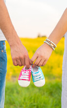 Pregnant Woman And Man Hold Baby Shoes. Selective Focus.