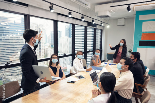 Businessman wearing face mask with presentation of business plan on laptop, corporate business meeting in modern office