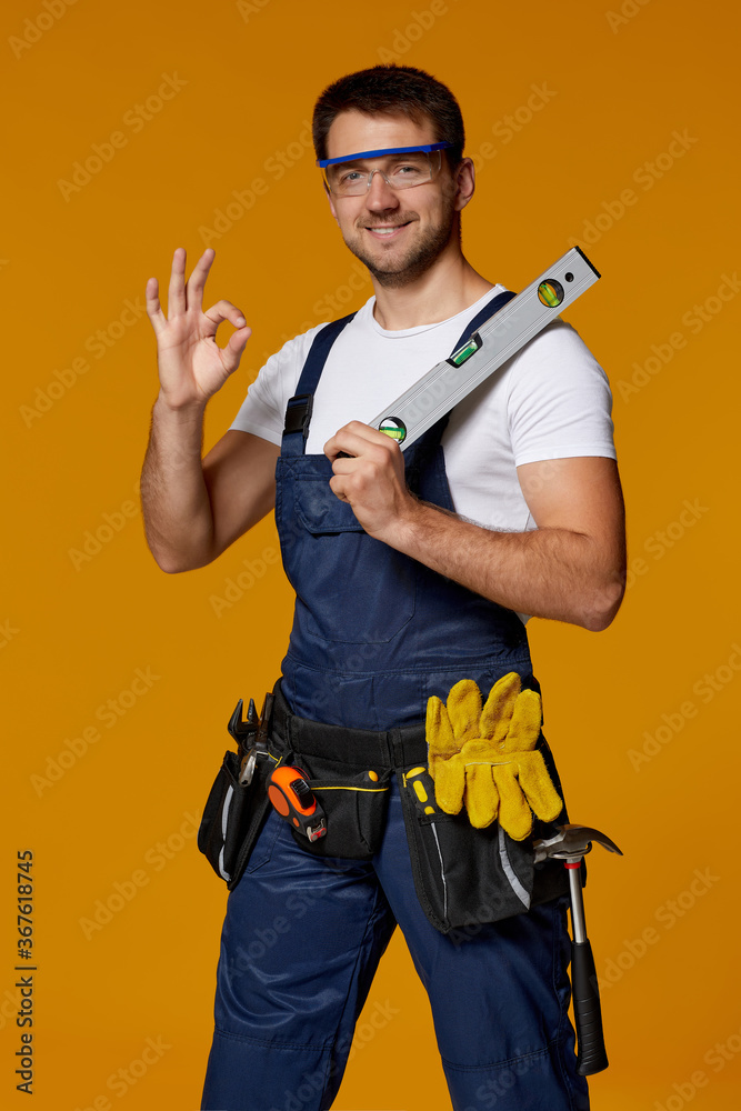 Fototapeta Young caucasian repairman worker in safety glasses and uniform holding builder level. handyman wearing tool belt showing Ok gesture isolated on orange studio background