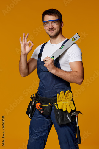 Obraz Young caucasian repairman worker in safety glasses and uniform holding builder level. handyman wearing tool belt showing Ok gesture isolated on orange studio background - fototapety do salonu