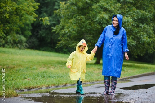 Obraz Mother with son walking in park in the rain wearing rubber boots - fototapety do salonu