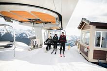 Friends Getting Off Ski Lift A...