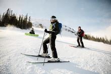 Portrait Female Skier And Sunny Snowy Mountain Ski Slope