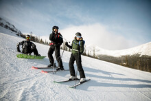 Skiers And Snowboarder Talking And Sunny Snowy Mountain Ski Slope