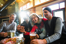 Happy Skier Couple Friends Taking Selfie And Drinking Beer In Ski Resort Lodge