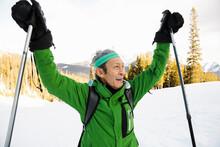 Happy Senior Man Raising Ski Poles On Snowy Mountain Ski Slope