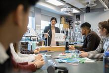 Female High School Teacher Explaining Wind Turbines To Students