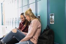 High School Students Using Smart Phone At Lockers