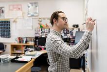 Male High School Teacher Writi...