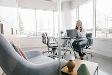 Woman Sitting At Desk Using La...