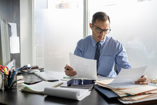 Male Doctor Reviewing Medical Charts At Desk In Office