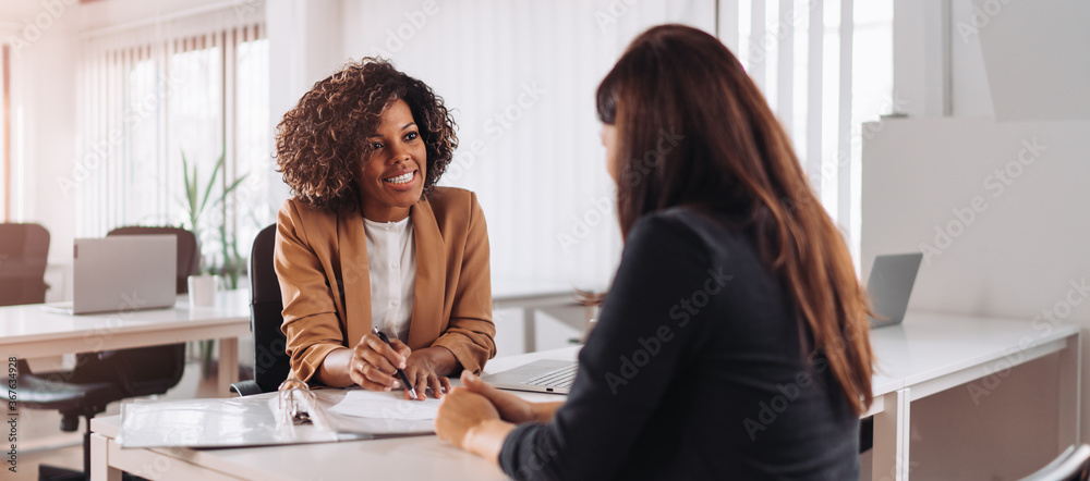 Fototapeta Woman consulting with a female financial manager at the bank