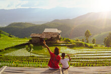 Happy Time Of Mother With Son Sitting On Wooden Bench And Enjoying Terrace Rice Fields At Bann Bong Piang In Mae Chaem, Chaing Mai, Thailand.