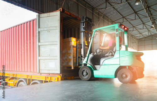 Fototapeta Forklift loading cargo shipment pallet goods into a truck container at dock warehouse. Cargo freight industry delivery warehouse logistics transportation. obraz