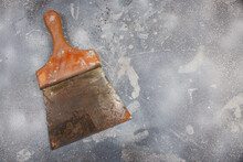 Old Painter's Spatula With Rust And Use Marks With Wooden Handle On Cement Background