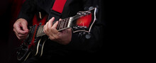 Guitarist Hands And Guitar On A Black Background Close Up. Playing Electric Guitar. Copy Spaces.