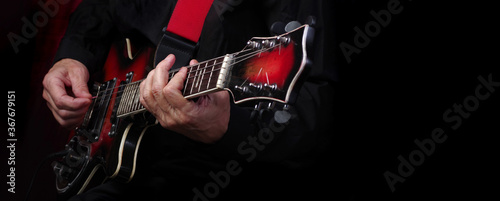 Obraz na plátně Guitarist hands and guitar on a black background close up