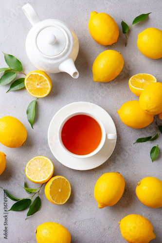 Tea cup and pot with lemon. Grey background. Top view.