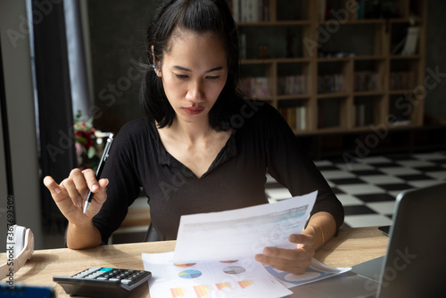 Business and Financial Planning Concept. Financial advisor planning and calculate budget, work on laptop. Professional Businesswoman discusses and analysis annual report at home office.