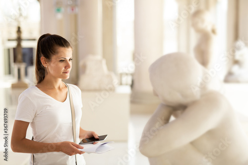 Fototapeta Portrait of young woman with guide brochure observing sculptures exposition in art museum obraz