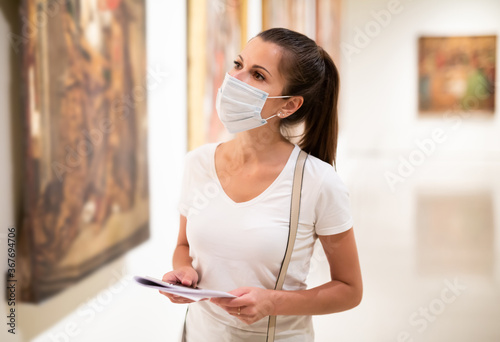 Fotografia, Obraz Focused adult girl in disposable face mask admiring paintings in museum holding