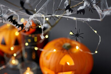 Halloween And Holiday Decorationsconcept - Jack-o-lantern Or Carved Pumpkin, Burning Candles, Electric Garland String, Spiders And Bats On Spiderweb