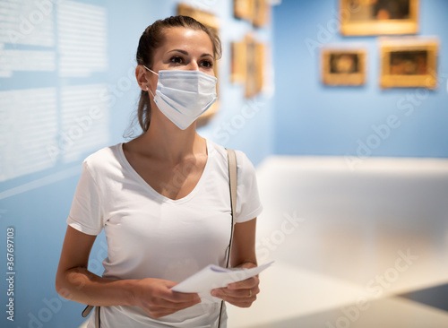 Obraz Young woman wearing face mask observing artworks in museum, new normal due to coronavirus outbreak - fototapety do salonu