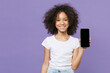 canvas print picture - Smiling little african american kid girl 12-13 years old in white t-shirt isolated on violet wall background studio portrait. Childhood lifestyle concept. Hold mobile phone with blank empty screen.