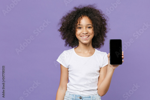 Fotografija Smiling little african american kid girl 12-13 years old in white t-shirt isolated on violet wall background studio portrait