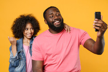 Cheerful African American Guy Girl Brother Sister In Denim Pink Clothes Isolated On Yellow Background Studio Portrait. People Lifestyle Concept. Mock Up Copy Space. Doing Selfie Shot On Mobile Phone.