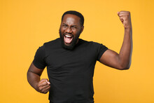 Overjoyed African American Man Guy Football Fan In Casual Black T-shirt Isolated On Yellow Wall Background Studio Portrait. People Lifestyle Concept. Mock Up Copy Space. Clenching Fists Like Winner.