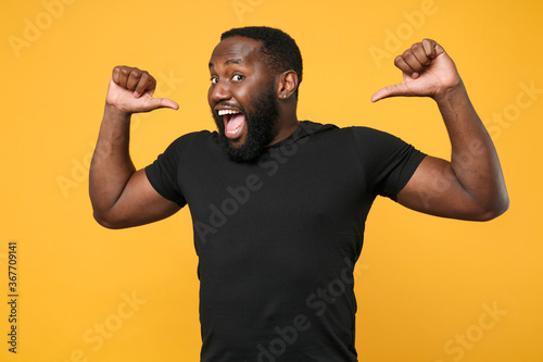 Fotografie, Tablou Excited african american man guy football fan in casual black t-shirt isolated on yellow background studio portrait