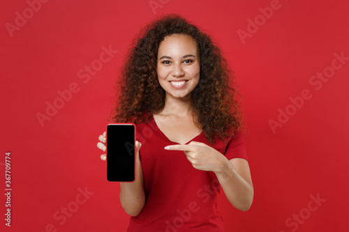 Fototapeta Smiling young african american girl in casual t-shirt posing isolated on red background. People lifestyle concept. Mock up copy space. Pointing index finger on mobile phone with blank empty screen. obraz