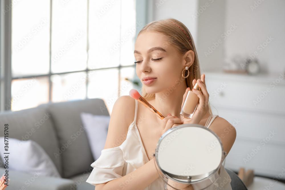 Fototapeta Beautiful young woman applying foundation at home