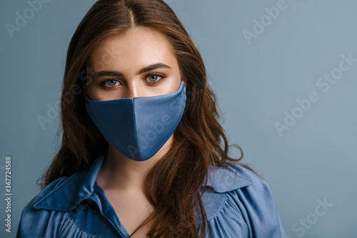 Woman wearing stylish protective blue face mask. Young beautiful brunette model. Trendy Fashion accessory during quarantine of coronavirus pandemic. Close up studio portrait. Copy, empty space - 367724588