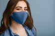 Beautiful Woman wearing stylish protective blue face mask. Trendy Fashion accessory during quarantine of coronavirus pandemic. Close up studio portrait. Copy, empty space for text