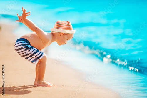Fotografie, Tablou Boy walking at sea in straw hat
