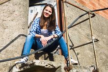 Portrait Of Female Wearing Jeans And Plaid Shirt Posing At Old Countryside Building
